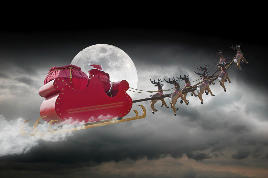 Santa Claus riding a sleigh led by reindeers on a cloudy night